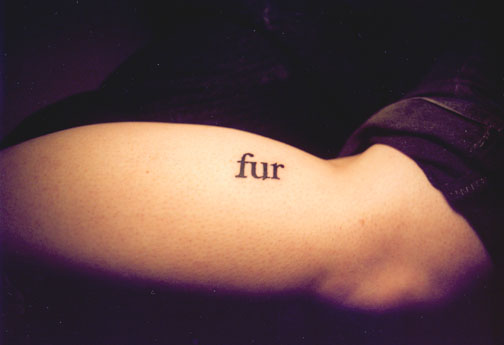 Human arm tattooed with the word fur