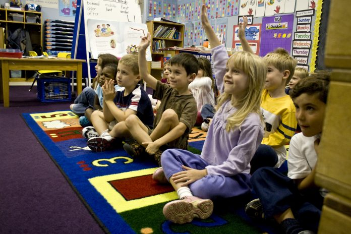 Kindergarten students raising their hands