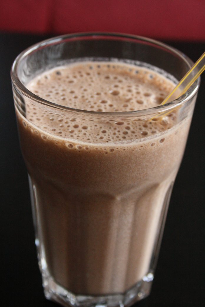 A glass of what appears to be possibly chocolate milk