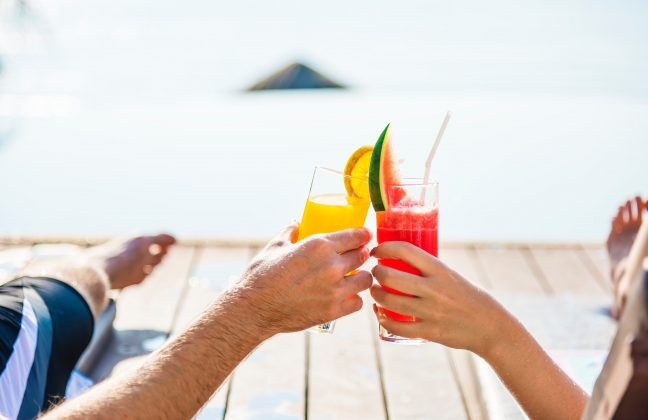 Two people toasting with cocktails