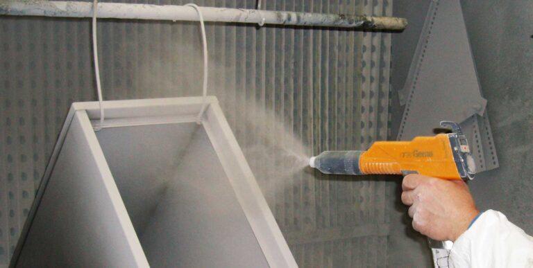 A powder coating gun in action