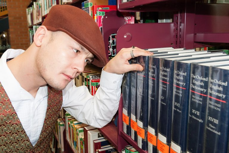 A man looking at a library shelf