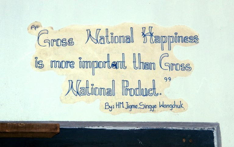 "Slogan painted on a wall: ""Gross National Happiness is more important than Gross National Product"" by Jigme Singye Wangchuck, King of Bhutan"