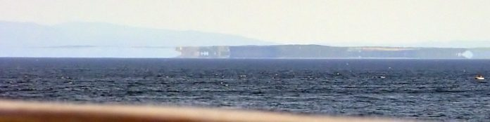 Fata Morgana seen on Norwegian coast: Just the hardly visible crest is on real position.
